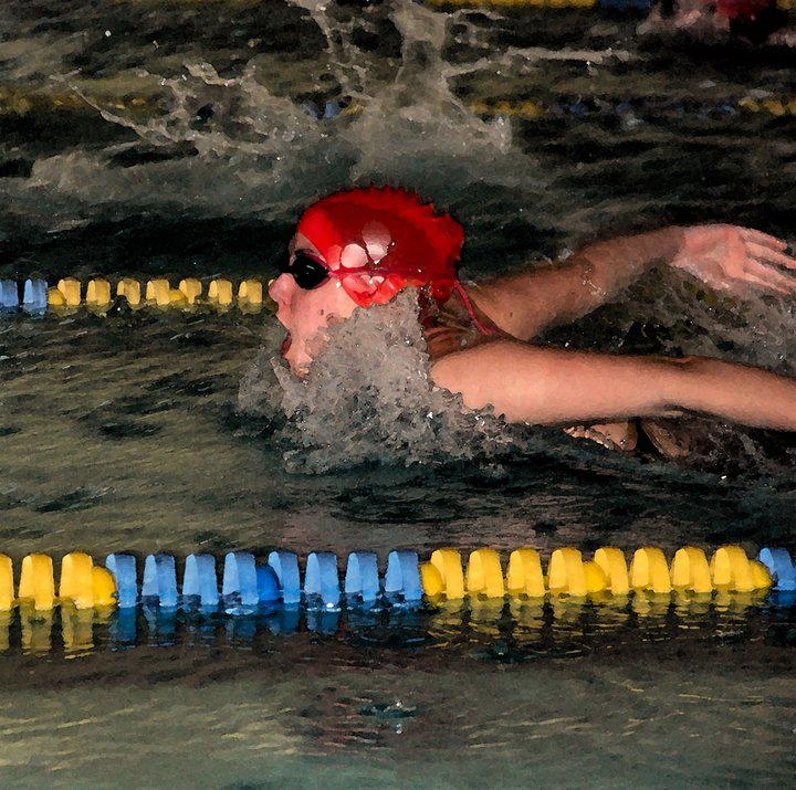 A swimmer with a swim cap on swimming laps.