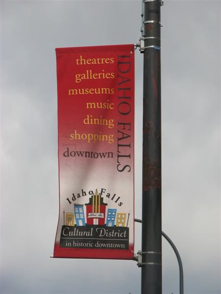 A banner hanging on a light pole advertising downtown.