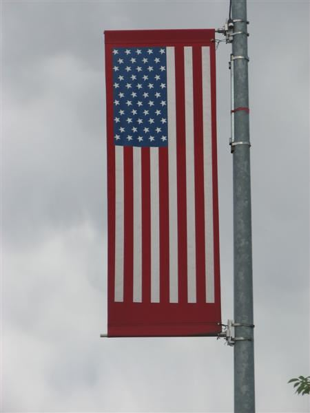 An American flag banner hanging from a light pole.